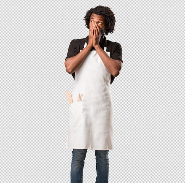 Hübscher afroamerikanerbäcker sehr erschrocken und ängstlich, hoffnungslos nach etwas, leidensschreie und offene augen, konzept des wahnsinns