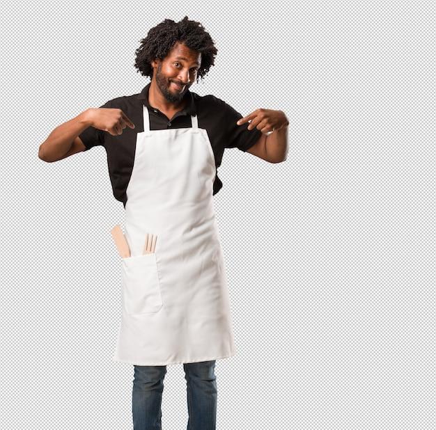 Hübscher afroamerikanerbäcker stolz und überzeugt, finger zeigend, um zu folgen, konzept der zufriedenheit, der arroganz und der gesundheit