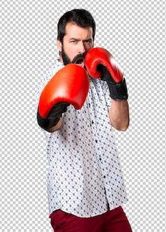 Hübscher brunettemann mit bart mit boxhandschuhen