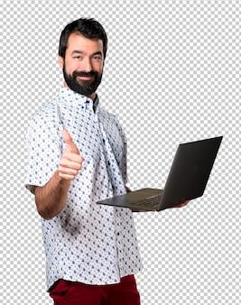 Hübscher brunettemann mit bart mit laptop