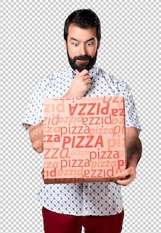 Hübscher brunettemann mit dem bart, der eine pizza hält