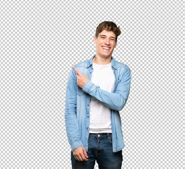 Hübscher junger mann, der auf die seite zeigt, um ein produkt darzustellen