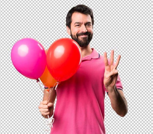 Hübscher junger mann, der ballone hält und drei zählt