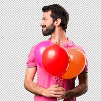 Hübscher junger mann, der ballone hält und seitlich schaut