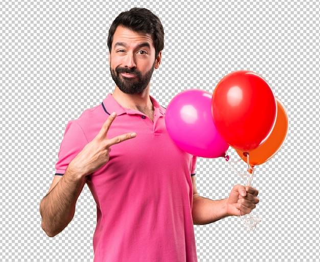 Hübscher junger mann, der ballone hält und sieggeste macht