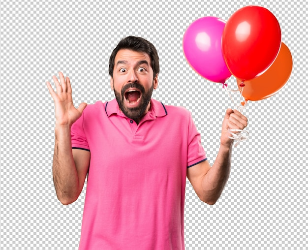 Hübscher junger mann, der ballone hält und überraschungsgeste macht