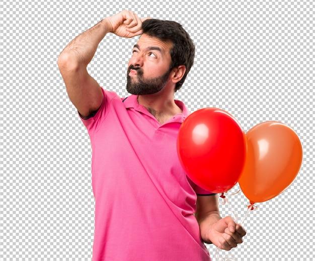 Hübscher junger mann, der ballone hält und zweifel hat