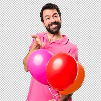 Hübscher junger mann, der ballone hält