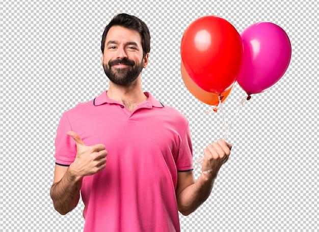 Hübscher junger mann, der ballone mit dem daumen oben hält