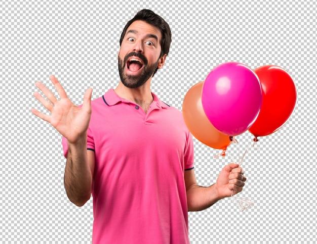 Hübscher junger mann, der ballone und begrüßung hält