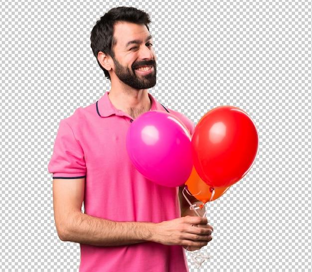 Hübscher junger mann, der ballone und das blinzeln hält