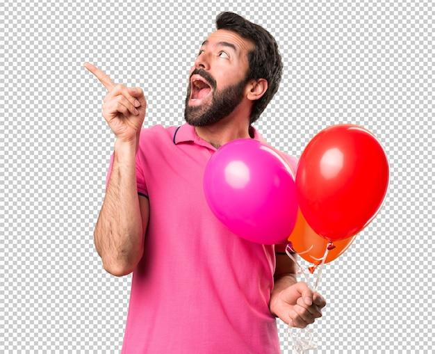 Hübscher junger mann, der ballone und das denken hält