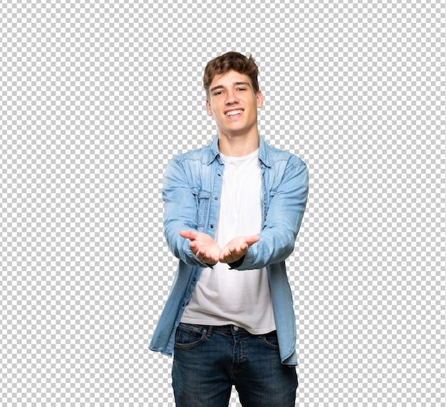 Hübscher junger mann, der copyspace eingebildet auf der palme hält, um eine anzeige einzufügen