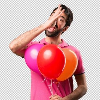 Hübscher junger mann, der einen witz hält ballone macht