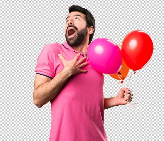 Hübscher junger mann in der liebe und ballone halten