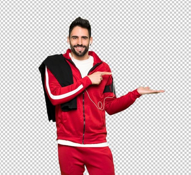 Hübscher sportler, der copyspace imaginär auf der palme hält, um eine anzeige einzufügen