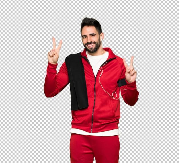 Hübscher sportler, der siegeszeichen mit beiden händen lächelt und zeigt