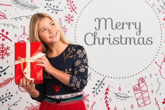 Hübsches mädchen mit eingewickeltem geschenk auf weihnachten