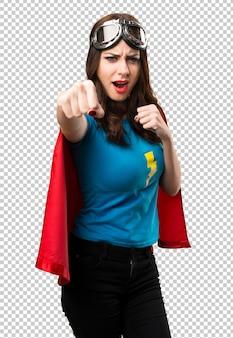 Hübsches superheldmädchen, das einen durchschlag gibt