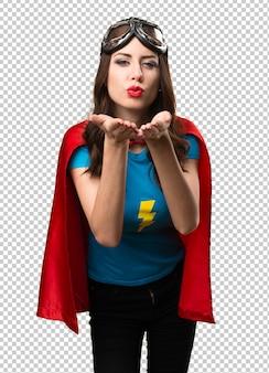 Hübsches superheldmädchen, das einen kuss sendet