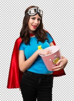Hübsches superheldmädchen, das popcorn isst