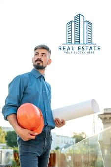 Immobilienmakler, der pläne für das neue gebäude hält