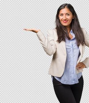 Indische frau des jungen geschäfts, die etwas mit den händen hält, ein produkt zeigt, und fröhlich lächelt und einen eingebildeten gegenstand anbietet