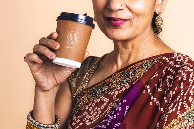 Indische frau in einem saree, die kaffee aus einem pappbechermodell trinkt