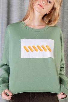 Intelligente frau mit grünem pullover vor einem vorhang