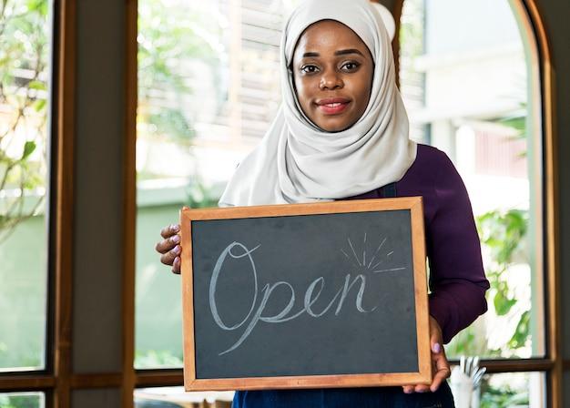 Islamischer kleinunternehmer der frau, der tafel mit dem lächeln hält