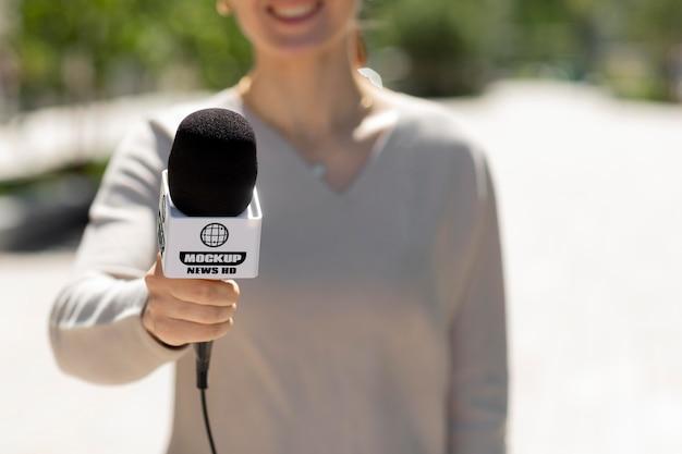 Journalist, der ein mikrofonmodell hält