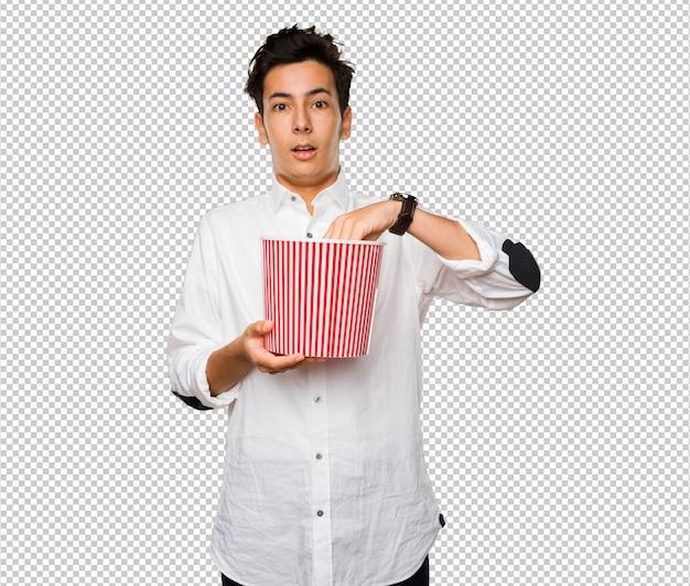 Jugendlicher, der einen popcorneimer hält