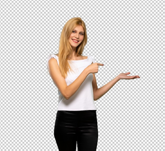 Junge blonde frau, die copyspace imaginär auf der palme hält, um eine anzeige einzufügen