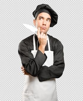 Junge chef mit einem kochutensilien mit einem zweifel geste