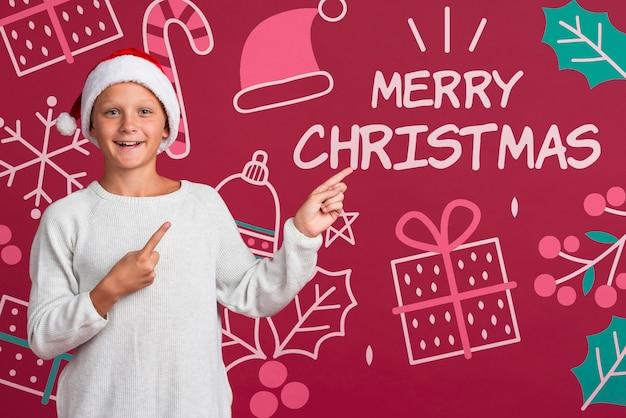 Junge, der auf mitteilung für weihnachten zeigt