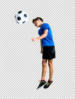 Junge, der den fußball schlägt den ball mit dem kopf spielt