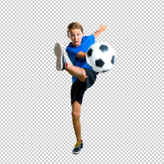 Junge, der den fußball tritt die kugel spielt