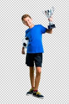 Junge, der fußball spielt und eine trophäe hält
