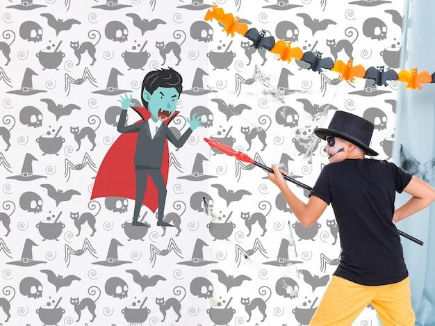 Junge, der mit gemaltem vampir auf der wandhalloween-party kämpft