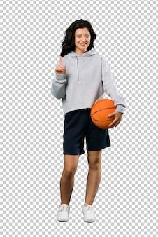 Junge frau, die den basketball oben zeigt eine großartige idee spielt