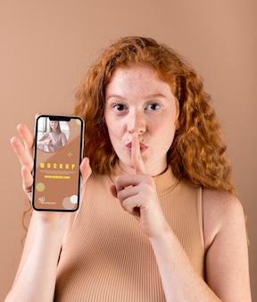 Junge frau, die ein smartphone-modell hält