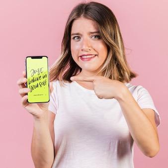 Junge frau, die finger auf ein mobiltelefonmodell zeigt