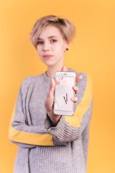 Junge frau, die smartphonemodell hält