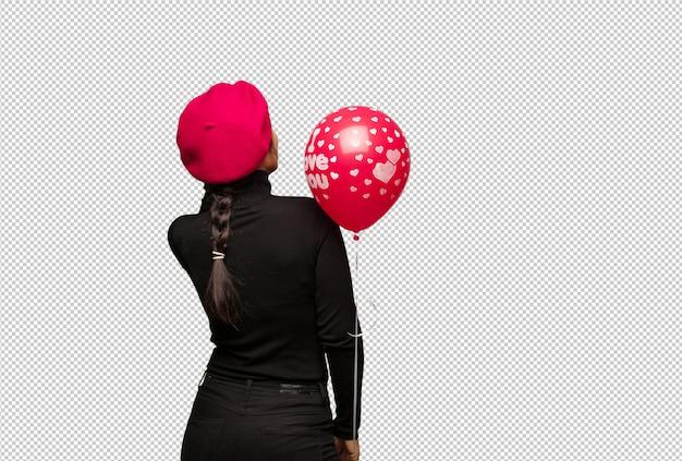 Junge frau im valentinsgrußtag von hinten denkend an etwas