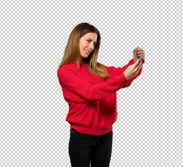 Junge frau mit der roten strickjacke, die ein selfie macht