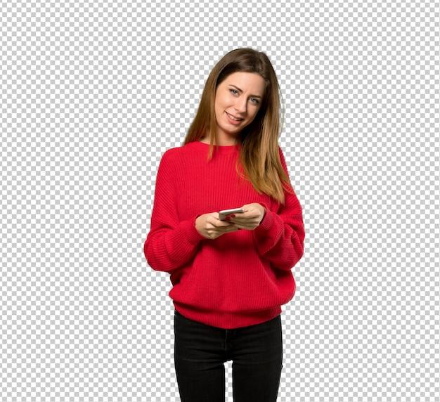 Junge frau mit der roten strickjacke, die eine mitteilung mit dem mobile sendet