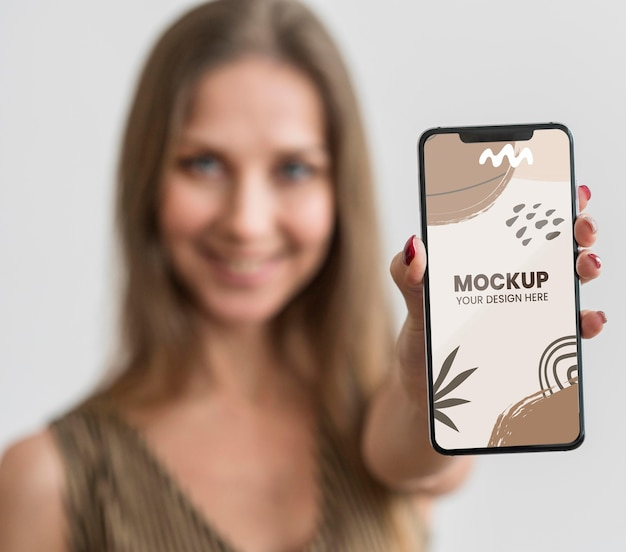 Junge frau mit einem smartphone-modell