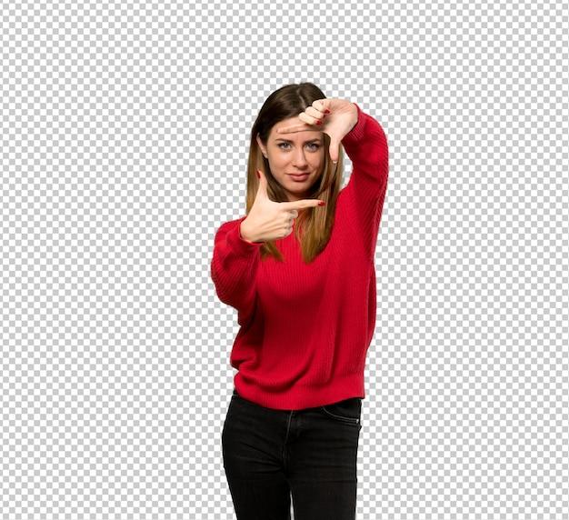 Junge frau mit fokussierendem gesicht der roten strickjacke. framing-symbol