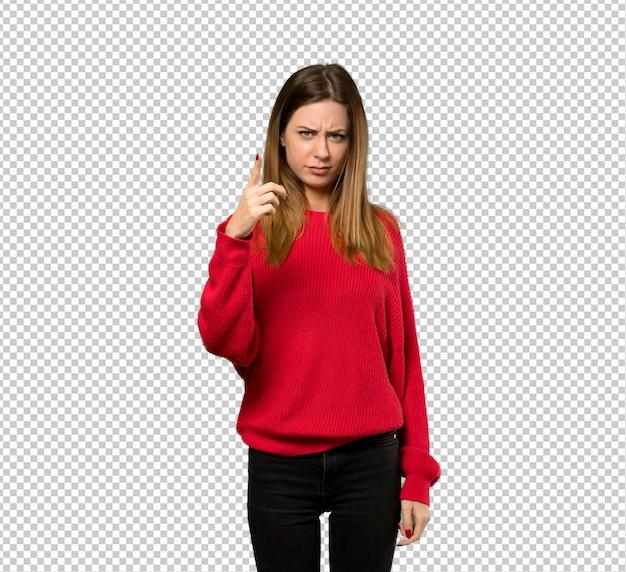 Junge frau mit roter strickjacke frustriert und auf die front zeigend