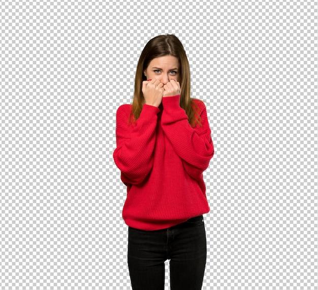 Junge frau mit roter strickjacke nervös und erschrocken, die hände zum mund setzend